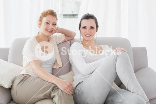 Two smiling female friends sitting on sofa in living room