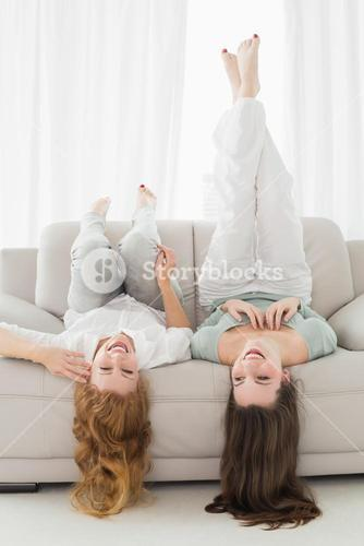 Female friends lying on sofa in the living room