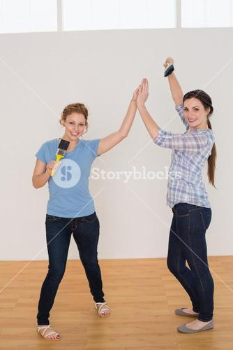 Female friends giving high five in a new house