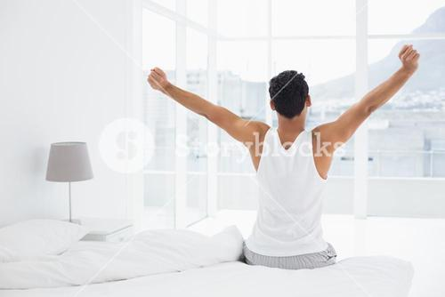 Rear view of a man stretching arms in bed