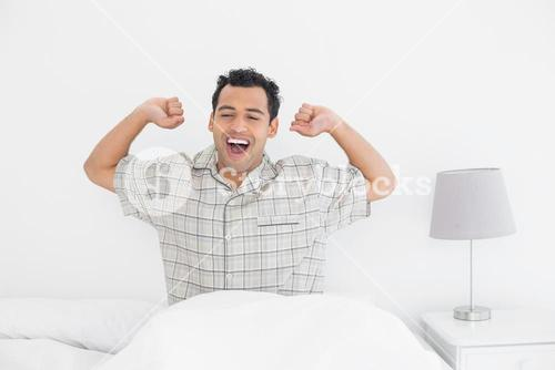 Smiling man stretching his arms in bed