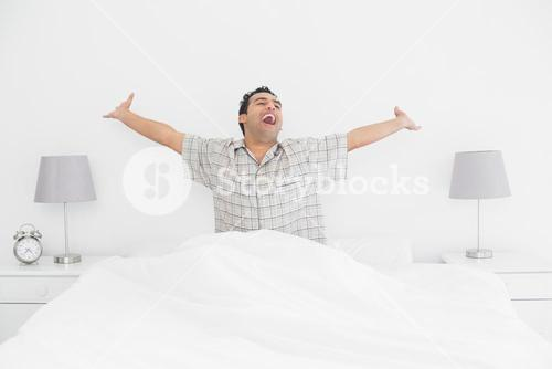 Cheerful man stretching his arms in bed