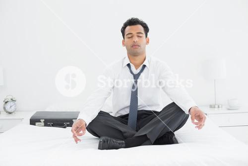Relaxed businessman sitting in lotus pose on bed