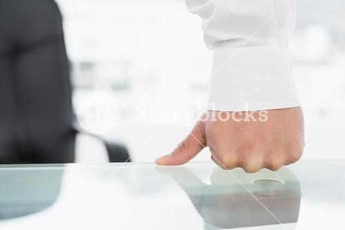 Mid section of a businessman with clenched fist on desk