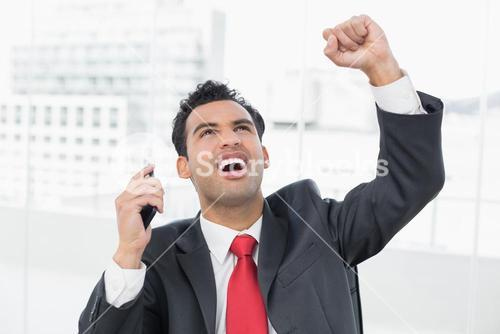 Businessman cheering with clenched fist as he looks up