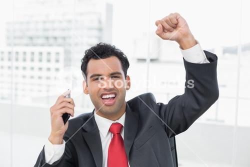 Businessman cheering with clenched fist at office