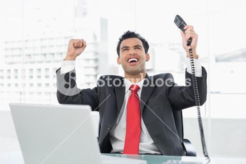Businessman cheering with telephone receiver at office