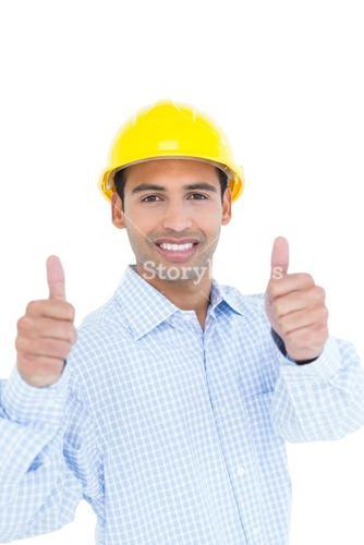 Smiling handyman in yellow hard hat gesturing thumbs up