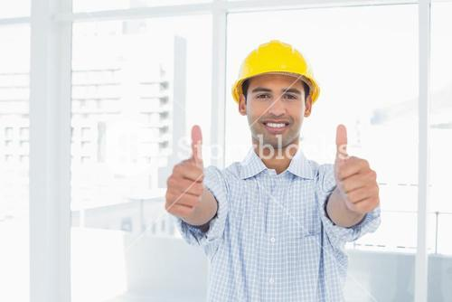 Handyman in yellow hard hat gesturing thumbs up in office