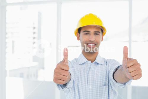Smiling handyman in yellow hard hat gesturing thumbs