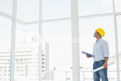 Handyman in hard hat with clipboard and blueprint looking at window