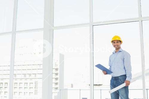 Handyman in hard hat with clipboard and blueprint in office