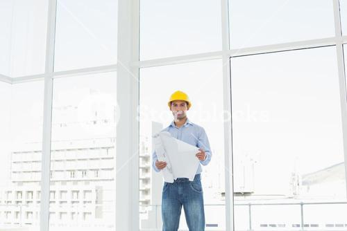 Architect in yellow hard hat with blueprint in office