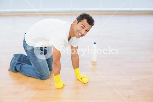 Smiling young man cleaning the parquet floor at house