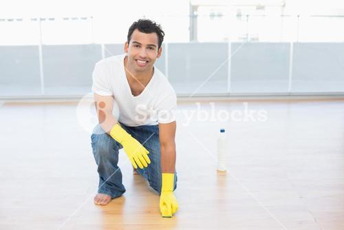 Smiling man cleaning the parquet floor at house