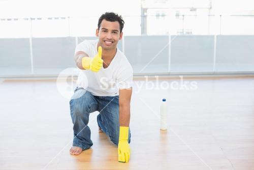 Man cleaning the floor while gesturing thumbs up at house