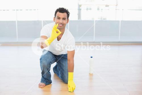 Smiling man cleaning the floor while gesturing okay sign