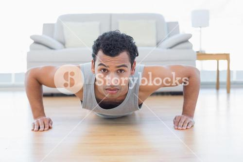 Sporty young man doing push ups in the living room