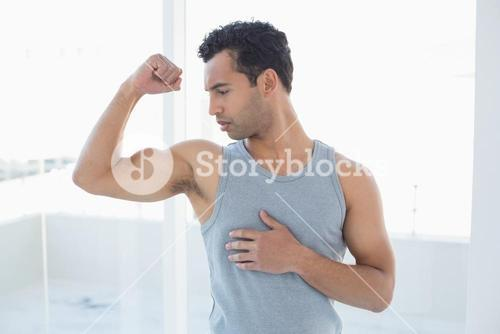 Fit young man flexing muscles in studio