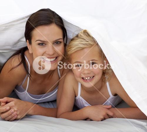Mother and daughter under the bedsheets