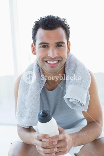 Man with towel around neck holding water bottle in fitness studio