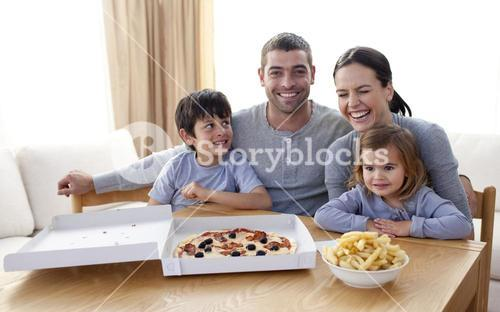 Family eating pizza and fries on a sofa