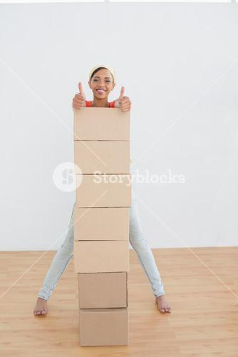 Smiling woman gesturing thumbs up with stack of boxes in new house