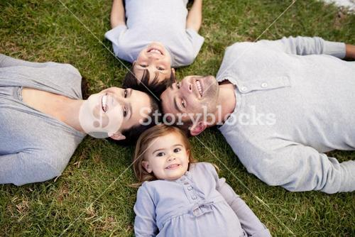 Family lying in a park with heads together
