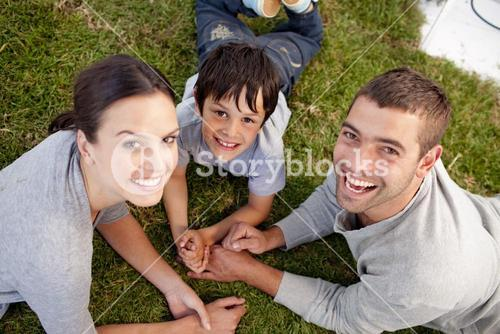 Parents and kid lying on garden