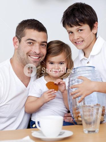 Father and children eating biscuits with milk