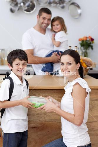 Radiant mother giving food to her son for lunch