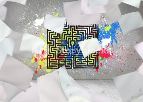 Papers in front of grey wall with maze and splashes