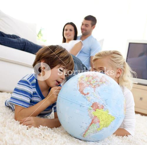 Children playing with a terrestrial globe in livingroom