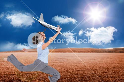 Composite image of happy businesswoman jumping while holding smartphone