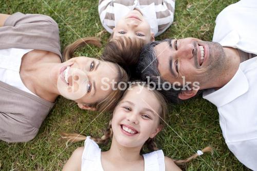 Smiling family lying outdoors