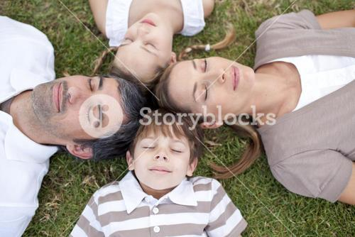 Family sleeping outdoors with heads together