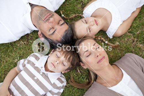 Family sleeping in a park with heads together