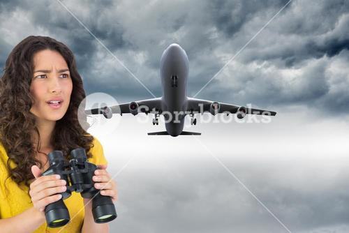 Composite image of serious young woman holding binoculars