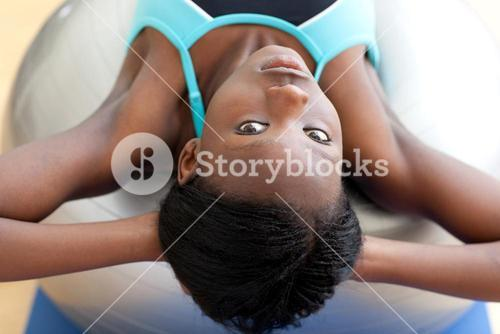 Serious woman doing situps with a pilates ball