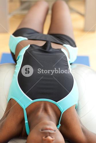 Woman doing situps with a pilates ball