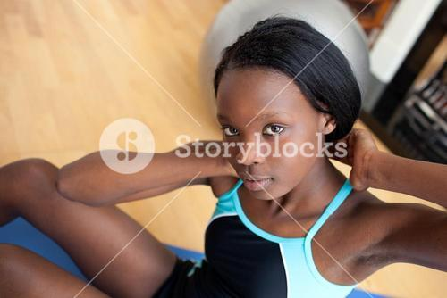 Beautiful woman in gym outfit doing situps