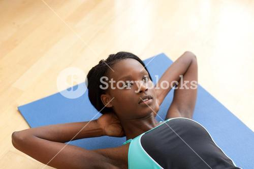 Charming woman in gym clothes doing situps
