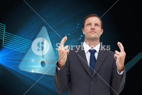 Composite image of businessman with fingers crossed is looking up