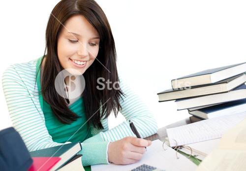 Smiling teen girl studying on a desk