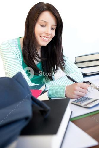 Cheerful teen girl studying on a desk