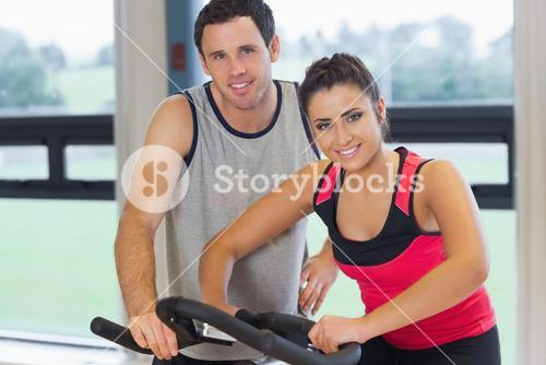 Trainer helping young woman work out at spinning class