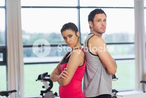 Serious young woman and man standing back-to-back in gym