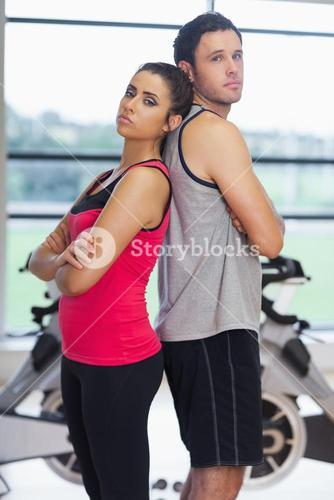 Serious woman and man standing back-to-back in gym