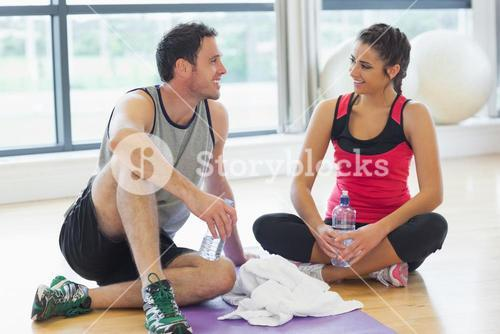 Woman and man with water bottles chatting at gym