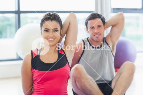 Two people stretching hands back behind at yoga class